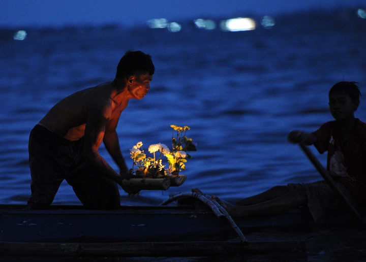 A survivor prepares to launch candle-filled mini boats made from sections of banana trees, as residents commemorate the first anniversary of the devastating Typhoon Haiyan in Tacloban City, central Philippines. Survivors of the strongest typhoon ever to hit land wept at mass graves on November 8, during ceremonies to mark one year since the storm devastated the central Philippines and condemned millions to deeper poverty. (Ted Aljibe/AFP-Getty Images)