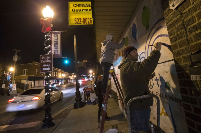 Local residents paint murals over boarded up businesses in Ferguson, Missouri November 27, 2014. Tensions eased in the St Louis suburb of Ferguson on Thursday after two nights of violence and looting sparked by racially charged anger over a grand jury's decision not to charge a white police officer for fatally shooting an unarmed black teenager. (Adrees Latif/Reuters)