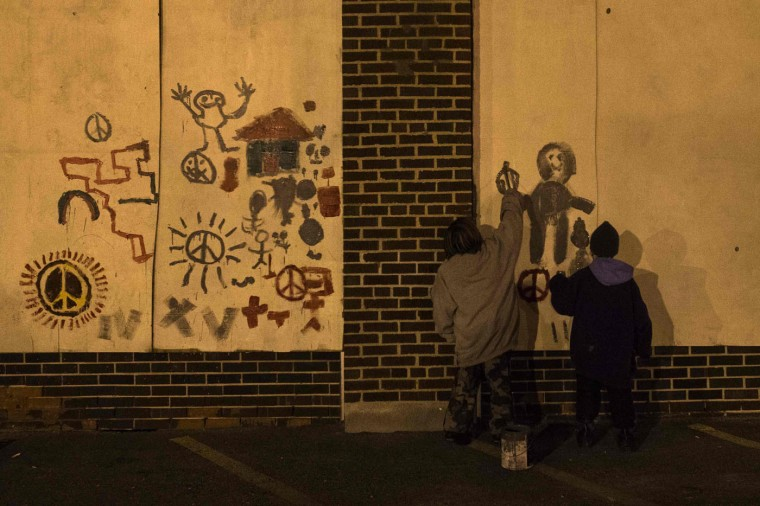 Boys paint murals over boarded-up businesses in Ferguson, Missouri November 27, 2014. Tensions eased in the St Louis suburb of Ferguson on Thursday after two nights of violence and looting sparked by racially charged anger over a grand jury's decision not to charge a white police officer for fatally shooting an unarmed black teenager. (Adrees Latif/Reuters)