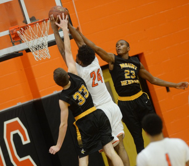 Mt. Hebron's Aaren Smith, right, and Nathan Stock, right, go up to block a shot from Oakland Mills' Will Robinson Jr. during a boys basketball game at Oakland Mills High School in Columbia, Monday, Dec. 8, 2014. (Jon Sham/BSMG)