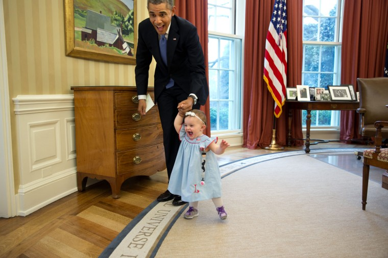 """April 4, 2014 """"Despite the haphazard framing, I love the expressions on the President and one-year-old Lincoln Rose Smith as she learns to walk in the Oval Office. This moment happened when former Deputy Press Secretary Jamie Smith and her family stopped by for a departure greet and photograph with the President."""" (Official White House Photo by Pete Souza)"""