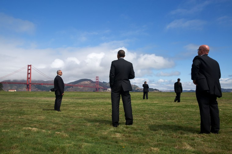 """July 23, 2014 """"Surrounded by Secret Service agents, the President views the Golden Gate Bridge in San Francisco. Rather than immediately board the Marine One helicopter at Crissy Field, the President instead walked right past the helicopter to see a better view of the bridge on a clear summer day."""" (Official White House Photo by Pete Souza)"""