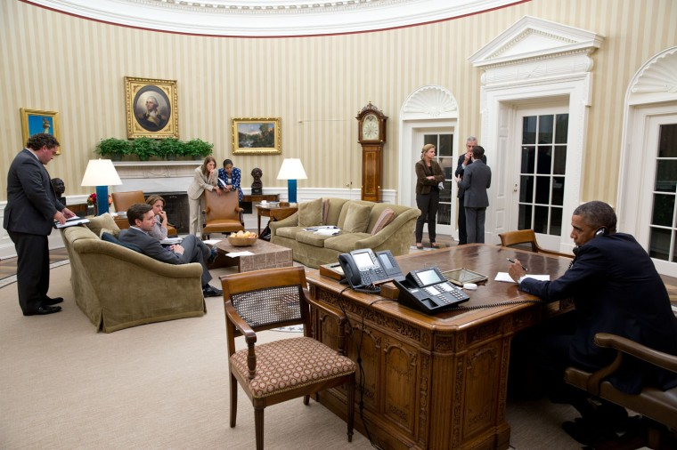 """Oct. 16, 2014 """"The President talks on the phone to Texas Gov. Rick Perry to make sure Texas had the necessary resources if more health-care workers became ill with the Ebola virus. Because there were several other people in the Oval Office, I tried to incorporate them into the photograph."""" (Official White House Photo by Pete Souza)"""