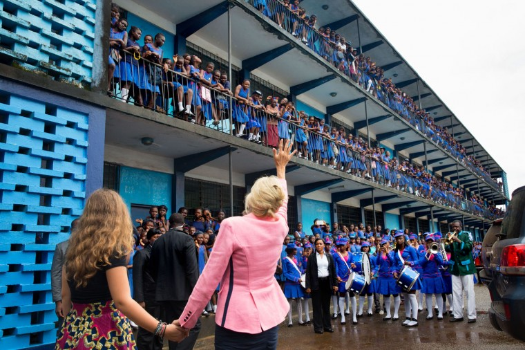 """July 7, 2014 """"David Lienemann accompanied Dr. Jill Biden on her summer trip to Africa. Here, Dr. Biden and granddaughter Finnegan Biden wave to students assembled on the railings after a girls education event at the St. Joseph's Secondary School in Freetown, Sierra Leone."""" (Official White House Photo by David Lienemann)"""