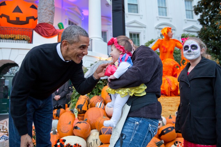 """Oct. 31, 2014 """"The President greets a youngster while he and the First Lady handed out Halloween treats to local children and children of military families at the White House."""" (Official White House Photo by Pete Souza)"""