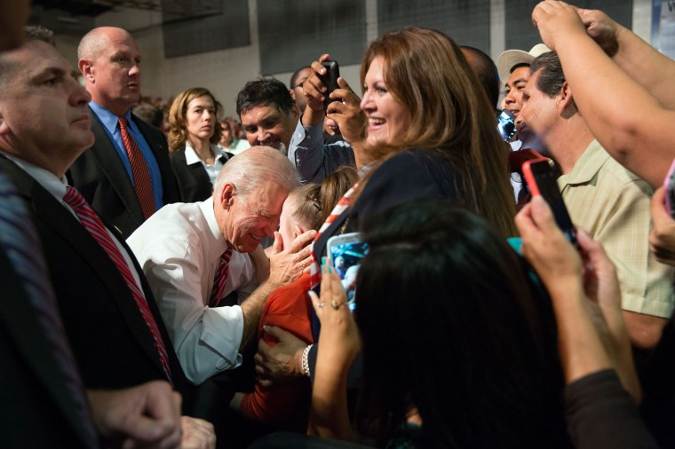 """Oct. 7, 2014 """"I love all the different things happening in this photograph by David Lienemann, with the main moment being the Vice President greeting a baby during a campaign rally in Bakersfield, California."""" (Official White House Photo by David Lienemann)"""