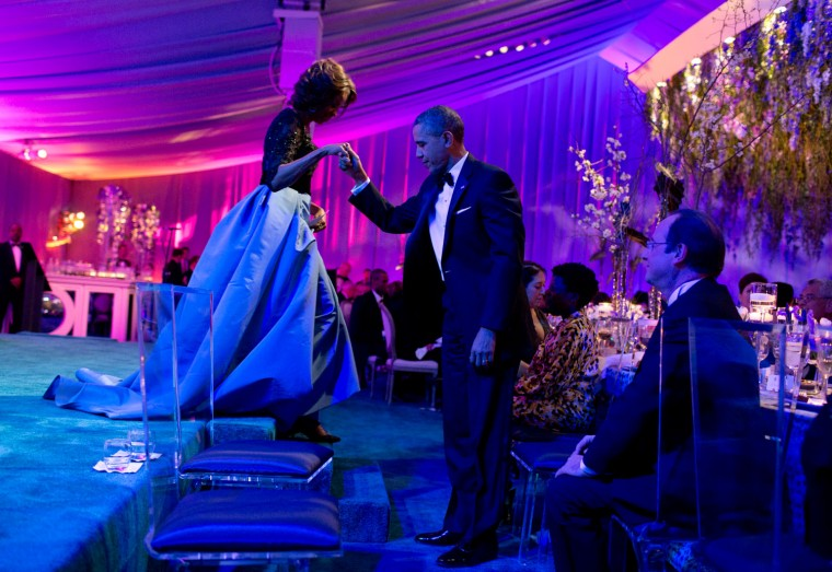 """Feb. 11, 2014 """"Ever the gentleman, the President helps the First Lady off the stage after she thanked the White House chefs during the State Dinner for President Franois Hollande of France on the South Lawn of the White House."""" (Official White House Photo by Pete Souza)"""