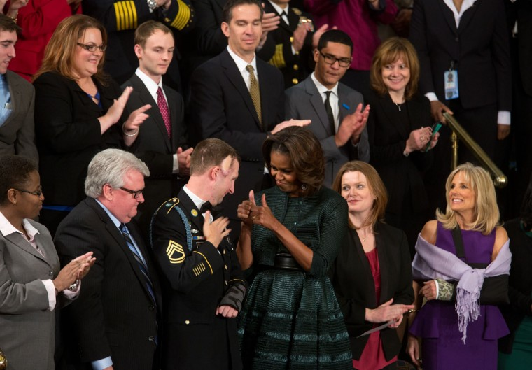 """Jan. 28, 2014 """"At the annual State of the Union address at the U.S. Capitol, Chuck Kennedy captured this poignant moment between the First Lady and U.S. Army Ranger Sgt. First Class Cory Remsburg. Cory first met the President in 2009 at a D-Day ceremony in Normandy. Four months later, Cory was badly injured in Afghanistan and in a coma for three months. In early 2010, shortly after Cory came out of his coma, the President happened to be visiting patients at Walter Reed Hospital. As he walked into one of the patient's rooms, hanging on the wall was a photo I had taken of the President and Cory in Normandy. The President then realized that he had met this badly injured Army Ranger at Normandy. Two years later, we were visiting Arizona, where Cory had gone home to further recuperate. The President asked if Cory would be able to greet him backstage. Amazingly, Cory was able to salute the President and walk across the room aided by a walker to shake hands with the President."""" (Official White House Photo by Chuck Kennedy)"""
