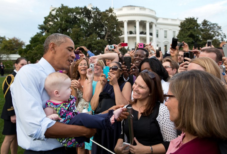 """Sept. 15, 2014 """"The President checks out a baby's foot while greeting guests at a picnic on the South Lawn of the White House."""" (Official White House Photo by Pete Souza)"""
