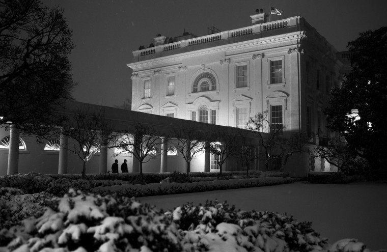 """Jan. 21, 2014 """"A blanket of snow in the Rose Garden made for an interesting foreground as the President walked along the White House colonnade to the residence at the end of his day accompanied by Chief of Staff Denis McDonough."""" (Official White House Photo by Pete Souza)"""
