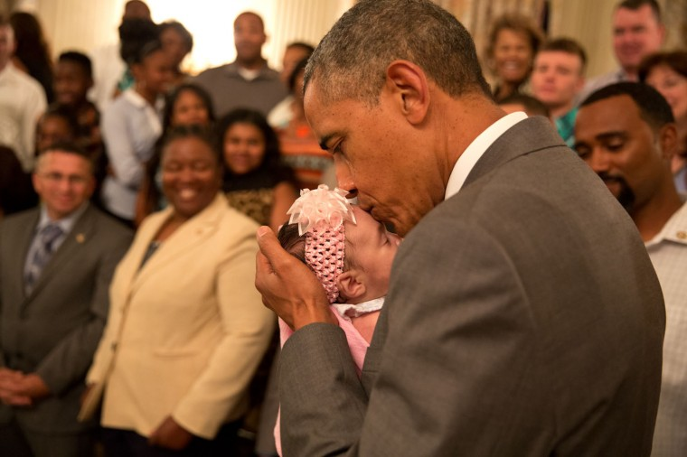 """June 23, 2014 """"The President kisses a baby girl as he and the Vice President greeted wounded warriors and their families during their tour in the East Room of the White House."""" (Official White House Photo by Pete Souza)"""