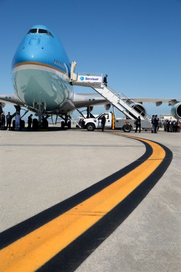"""July 23, 2014 """"Occasionally, a graphic element becomes the key factor in an interesting photograph. Here, at Los Angeles International Airport, I ran out in front of Air Force One to preposition myself at a low angle to take advantage of the yellow stripe as the President walked off the plane."""" (Official White House Photo by Pete Souza)"""