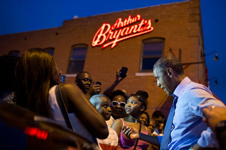 """July 29, 2014 """"Sometimes you get lucky as a photographer. The President was greeting the crowd outside Arthur Bryant's Barbeque in Kansas City. As he began talking to a young boy, actually giving him some life advice, someone's smart phone briefly illuminated the President's face. Without this light, the photograph wouldn't have been nearly as successful."""" (Official White House Photo by Pete Souza)"""