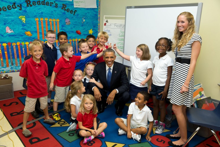 """Sept. 17, 2014 """"'Don't make rabbit ears', the President said to a group of students before taking a photo with them. Which of course some of them couldn't resist doing. I especially love the girl with her arm wrapped around the President's arm. The students were from an elementary school at MacDill Air Force Base in Tampa, Florida."""" (Official White House Photo by Pete Souza)"""