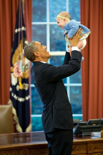 """Oct. 14, 2014 """"The President lifts the daughter of a departing staff member in the Oval Office."""" (Official White House Photo by Pete Souza)"""