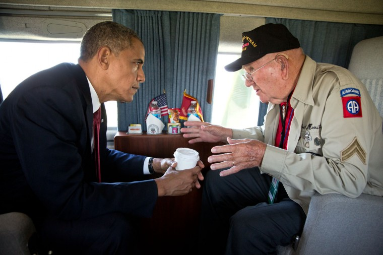 """June 6, 2014 """"This isn't so much a great photograph as it was just an honor to be in the presence of World War II veteran Kenneth (Rock) Merritt as he regaled stories of D-Day to President Obama aboard Marine One on the 70th French-American Commemoration D-Day Ceremony. The President invited 'Rock' to fly on the helicopter after leaving the Normandy American Cemetery and Memorial in Colleville-sur-Mer, France."""" (Official White House Photo by Pete Souza)"""