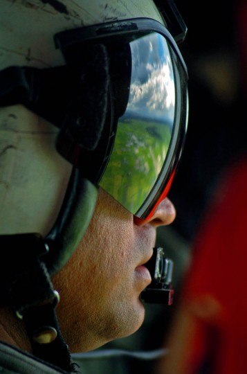 The land below is reflected on the protective goggles of Navy AM1 George Hokanson who stares out at the landscape from a Navy SH- 605 helicopter based on the USNS San Jose that flies food to Lhok Nga residents Tuesday, Jan. 18, 2005 following a tsunami that swept through the town in December. (Karl Merton Ferron, Baltimore Sun)