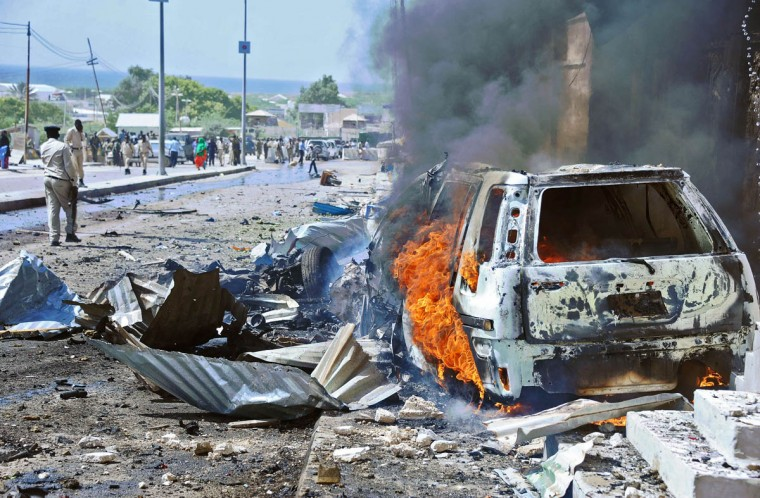 A car burns following a blast near the heavily fortified gates of the airport in Mogadishu on December 3, 2014. At least four people were killed in Somalia's capital Mogadishu when a suicide bomber rammed a car packed with explosives into a UN convoy, police said. The convoy of armoured vehicles were reportedly ferrying staff between Mogadishu's heavily-fortified airport and a protected UN base in the city when it was hit close to the airport gate. (Mohamed Abdiwahab/Getty Images)