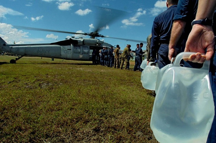 United States military personnel create a human conveyor on a soccer field to get water on board helicopters that will carry the items to remote areas affected by the tsunami from the city's airport Tuesday, Jan. 18, 2005 following a tsunami that swept through the town in December. (Karl Merton Ferron, Baltimore Sun)