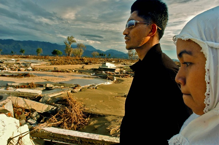 Mimi and husband Pendi stand at what is left of her parents' home Tuesday, Jan. 18, 2005 following a tsunami that swept through the town in December. Mimi's father was spared, but she lost other members of her family. (Karl Merton Ferron, Baltimore Sun)