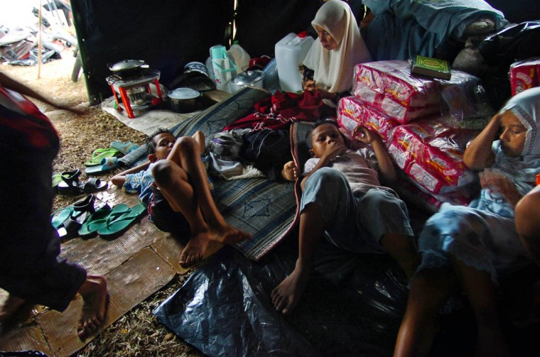 With a lack of privacy in a military tent filled with displaced people, Humaira Puspitadewi, 11 (right) makes a fruitless attempt at napping on bricks of diapers with her brother Ahmad Chumaini, 9 (center) and brother- in- law TM Hasan Basri, 9, who relaxes while the aunt, Hayatun (background) mends clothing. (Karl Merton Ferron, Baltimore Sun)