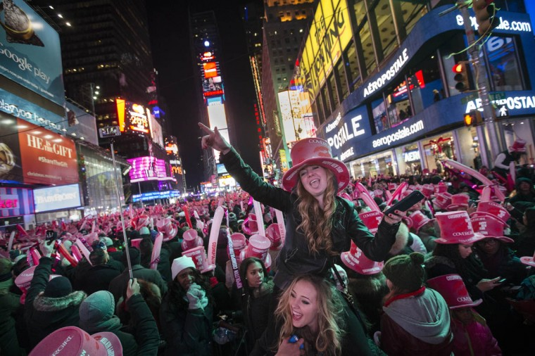 Katlyn Bond, of Somers, N.Y., cheers in Times Square during a New Year's Eve celebration, Thursday, Jan. 1, 2015, in New York. Thousands braved the cold to watch the annual ball drop and ring in the new year. (John Minchillo/AP photo)