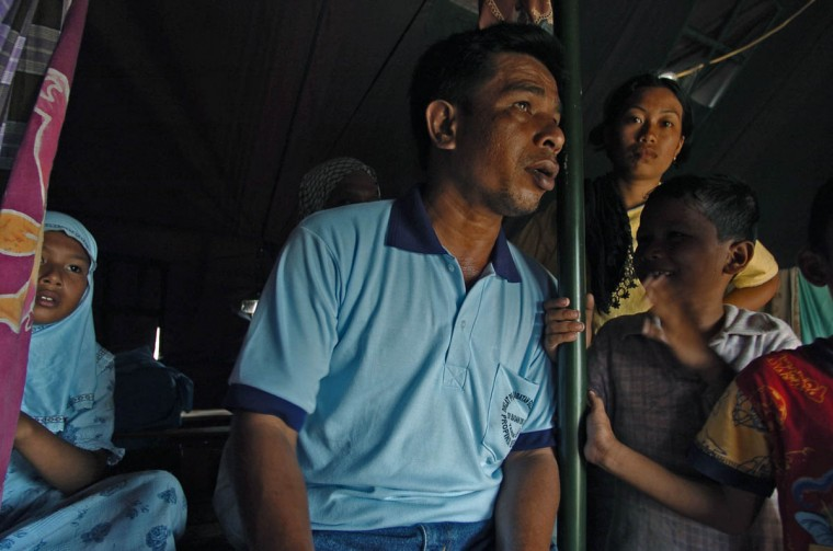 Humaira, 11 (left) sits in the community tent behind her father as they attempt to get back on their feet January 16, 2005 after a tsunami destroyed their home and disrupted their lives in December. (Karl Merton Ferron, Baltimore Sun)