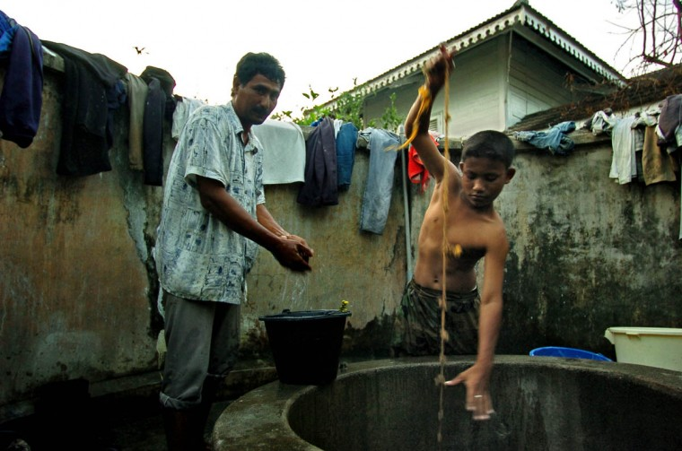 Dasril (left) prepares to wash as Henrda, 15 dips in to the well for water at Rukoh village's shelter Friday, Jan. 14, 2004. (Karl Merton Ferron, Baltimore Sun)