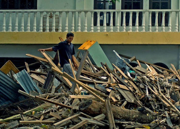 Piles of debris from demolished property from the December tsunami reach close to the second level as a homeowner surveys the amount of work that needs to be done Friday, Jan. 14, 2004. (Karl Merton Ferron, Baltimore Sun)