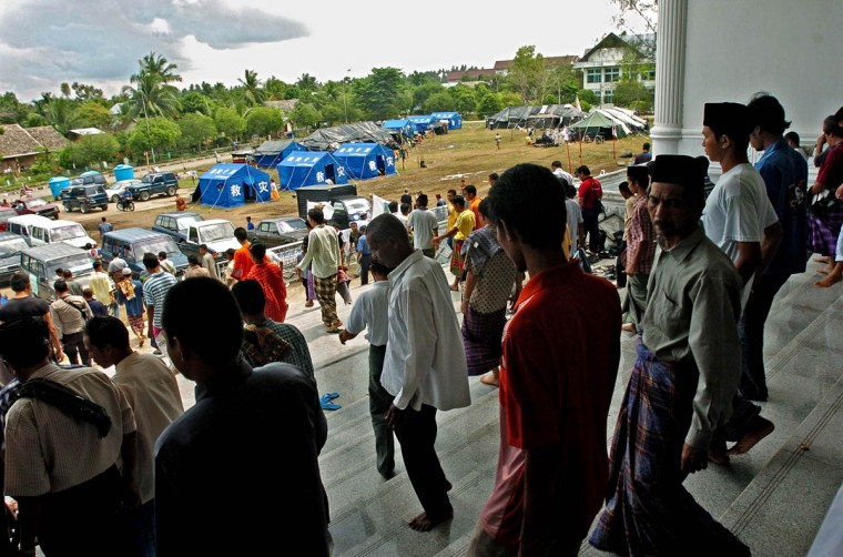 Muslims attending Friday prayer exit Masjid Kopelma Darussalam as tents for the displaced await many of them as temporary homes Friday, Jan. 14, 2004. (Karl Merton Ferron, Baltimore Sun)
