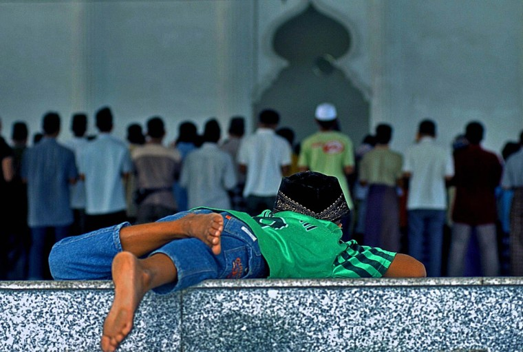 Already having taken part in Friday prayer which included the speaker talking about the tsunami disaster, a child watches the adults continue at Masjid Kopelma Darussalam Friday, Jan. 14, 2004. (Karl Merton Ferron, Baltimore Sun)