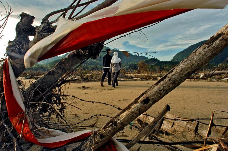 Pendi and his wife Mimi are framed in the colors of the Indonesia, caught in a barbed wire fence as they head for her parents' destroyed home to search for mementos Tuesday, Jan. 18, 2005 following a tsunami that swept through the town in December. (Karl Merton Ferron, Baltimore Sun)