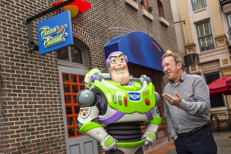 "In this handout photo provided by Disney Parks, actor and comedian Tim Allen, the voice of Buzz Lightyear in the Disney-Pixar ""Toy Story"" series of animated films, poses with Buzz Lightyear December 31, 2014 at Disney's Hollywood Studios theme park in Lake Buena Vista, Florida. Allen, who also starred on the hit TV series ""Home Improvement"" and in live-action motion pictures like ""The Santa Clause,"" is visiting the Walt Disney World Resort to ring in the new year. (Photo by Matt Stroshane/Disney Parks via Getty Images)"