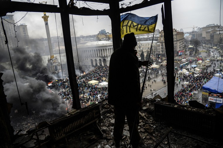 """A protester holds an Ukranian national flag from a burned building during a face-off against police on February 20, 2014 in Kiev. Ukraine's embattled leader announced a """"truce"""" with the opposition as he prepared to get grilled by visiting EU diplomats over clashes that killed 26 and left the government facing diplomatic isolation. The shocking scale of the violence three months into the crisis brought expressions of grave concern from the West and condemnation of an """"attempted coup"""" by the Kremlin. Bulent Kilic/AFP/Getty Images"""