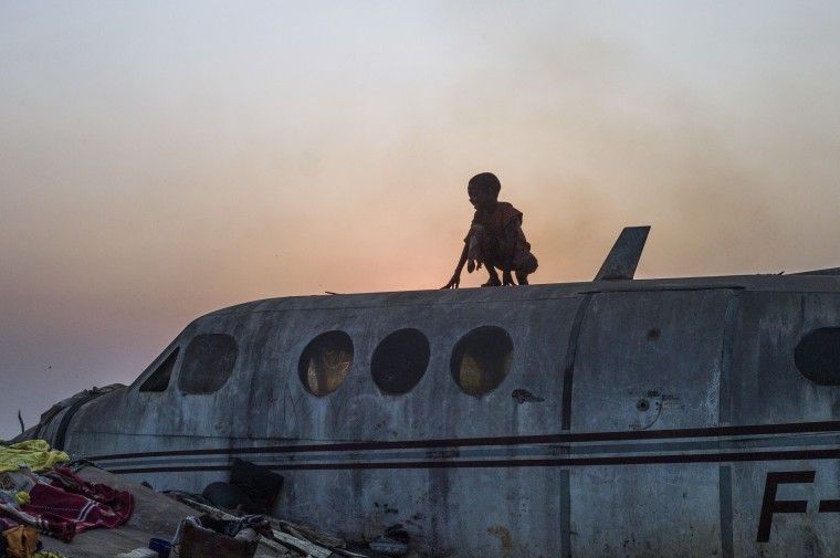 """A boy stands on an airplane in the Christian Mpoko refugee camp on February 20, 2014 during sunset, in Bangui, Central African Republic. Interim President Samba Panza has vowed to """"go to war"""" on the anti-balaka, who claim to seek vengeance for atrocities committed by a mainly Muslim rebel alliance, the Seleka, which temporarily seized power in March last year. The Seleka coup plunged the country into chaos, unleashing a wave of Muslim-Christian violence that has left thousands dead. Hundreds of thousands of people have also been displaced by the brutal surge of killings, mutilations, rapes and looting. Fred DuFour/AFP/Getty Images"""