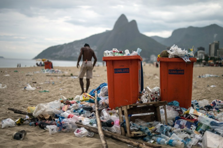A man walks next to full trash cans on Ipanema beach during a strike by some garbage collectors in Rio de Janeiro, Brazil on March 6, 2014. Rio de Janeiro's cleaners got a police escort as they pursued their post-Carnival sweep up after some striking colleagues reportedly threatened them, in some cases with guns, authorities said. Yasuyoshi Chiba/AFP/Getty Images