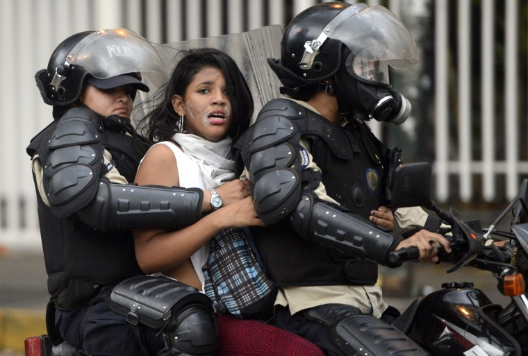 """An anti-government activist is arrested by national police during a protest against Venezuela President Nicolas Maduro government in Caracas on March 13, 2014. A total of 28 people have been killed and 365 injured in anti-government protests rocking Venezuela, the country's top prosecutor said Thursday, lamenting an atmosphere of """"violence and chaos"""". Leo Ramirez/AFP/Getty Images"""