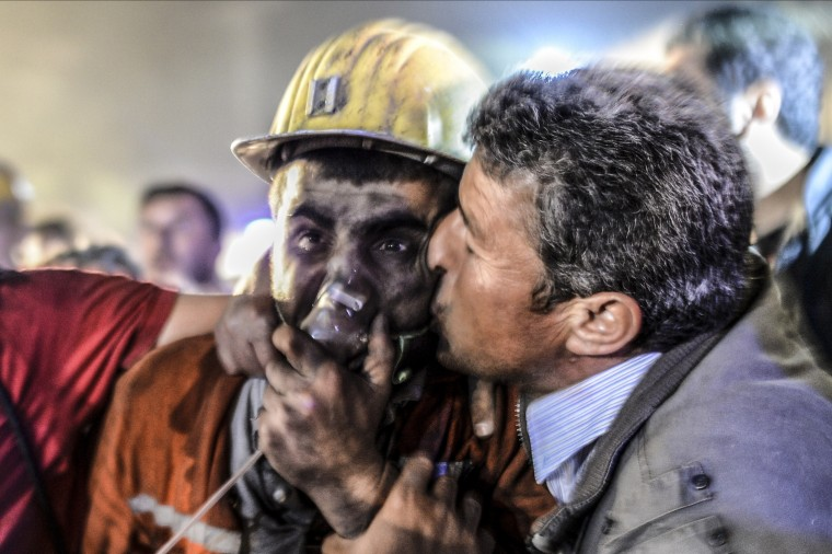 """A man kisses his son, rescued of the mine, on May 13, 2014 after an explosion in a coal mine in Manisa. At least 157 miners were killed in collapsed coal mine in the western Turkish city of Manisa. """"At least 200-300 workers were working in the mine when an electric fault caused an explosion,"""" the mayor of Soma, a district of Manisa, told private NTV television. BULENT KILIC/AFP/Getty Images"""