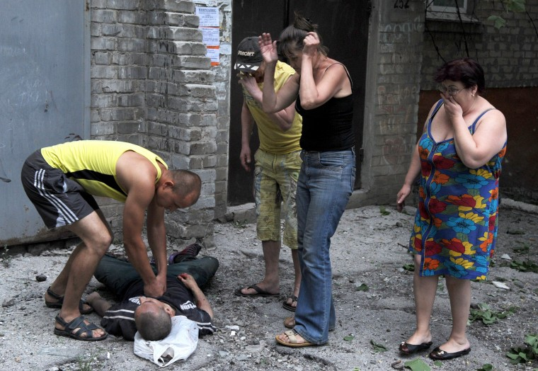 Perople react as a man attempts to revive another, wounded as a result of fighting between pro-Russian separatists and Ukrainian troops in the eastern Ukrainian city of Slavyansk on May 26, 2014. A fierce battle erupted on May 26 for control of the main airport in rebel-held eastern Ukraine, just hours after president-elect Petro Poroshenko vowed he would not let the country become another Somalia. VIKTOR DRACHEV/AFP/Getty Images