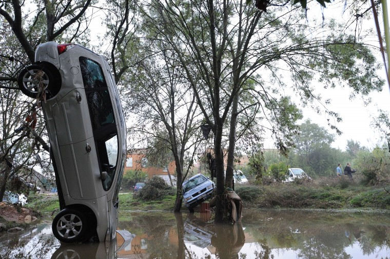 A picture taken on October 7, 2014 in Grabels near Montpellier shows a car in an upright position following the overnight flash floods due to heavy showers. Floodwater streamed down roads and highways, engulfing cars as the Lez river burst its banks in the seaside capital of the Languedoc-Roussillon region after it was lashed by record-breaking downpours. SYLVAIN THOMAS/AFP/Getty Images
