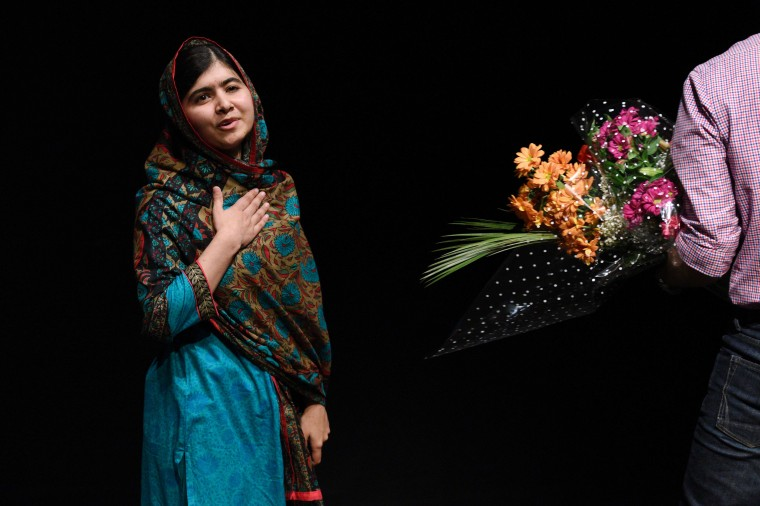 """Pakistani rights activist Malala Yousafzai gestures after addressing the media in Birmingham, central England on October 10, 2014. The Nobel Peace Prize went Friday to 17-year-old Pakistani Malala Yousafzai and India's Kailash Satyarthi for their work promoting children's rights. Seventeen-year-old Nobel Peace Prize winner Malala Yousafzai said she was """"honoured"""" to be the first Pakistani and the youngest person to be given the award and dedicated the award to the """"voiceless"""". """"This award is for all those children who are voiceless, whose voices need to be heard,"""" she said. OLI SCARFF/AFP/Getty Images"""