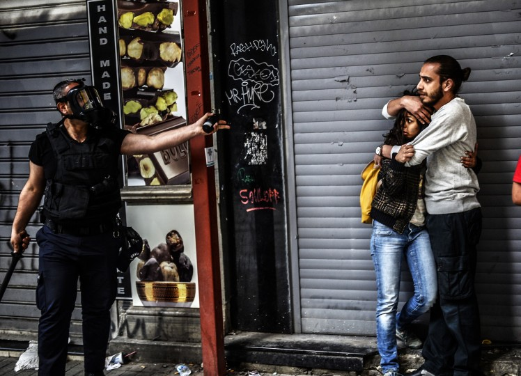 """A man protects a woman as they face a police officer dispersing protesters who gathered on the central Istoklal avenue near Taksim square in Istanbul, on May 31, 2014, as the police blocked access to the square during the one year anniversary of the Gezi park and Taksim square demonstrations. Turkey's combative prime minister warned protesters that police would do """"whatever is necessary"""" to clamp down on demonstrations today in Istanbul's Taksim Square to mark the anniversary of last year's turmoil. Last year, what started as a small campaign to save the nearby Gezi Park from the bulldozers eventually drew an estimated three million protesters in an outpouring of anger at the perceived authoritarian tendencies of Erdogan's Islamic-rooted government. Eight people died and thousands were injured in the ensuing violence as police launched a brutal crackdown, frequently employing tear gas and water cannons. BULENT KILIC/AFP/Getty Images"""