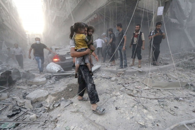 """A Syrian man carries two girls covered with dust following a reported air strike by government forces on July 9, 2014 in the northern city of Aleppo. According to the Syrian Observatory for Human Rights, by May some 2,000 civilians including 500 children had been killed in the daily air strikes, which rights groups have condemned as a """"war crime"""" for failing to discriminate between military and civilian targets. ZEIN AL-RIFAI/AFP/Getty Images"""