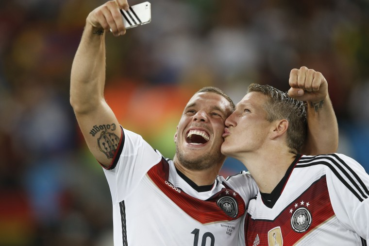 Germany's midfielder Bastian Schweinsteiger (R) and Germany's forward Lukas Podolski (C) take a 'selfie' after their victory in extra-time in the final football match between Germany and Argentina for the FIFA World Cup at The Maracana Stadium in Rio de Janeiro on July 13, 2014. ADRIAN DENNIS/AFP/Getty Images