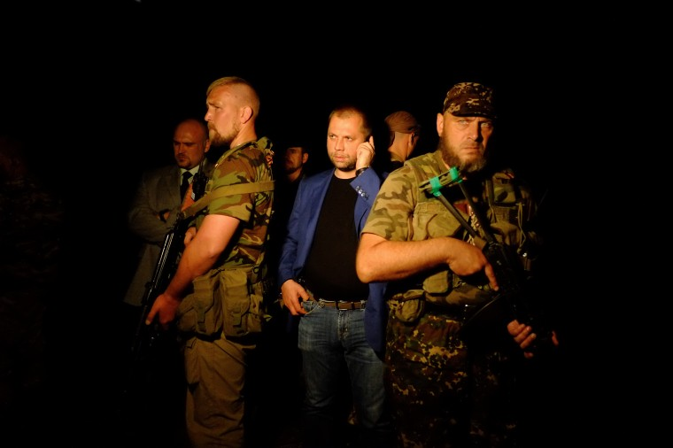 """Self-proclaimed Prime Minister of the pro-Russian separatist """"Donetsk People's Republic"""" Alexander Borodai (C) stands as he arrives on the site of the crash of a malaysian airliner carrying 298 people from Amsterdam to Kuala Lumpur, near the town of Shaktarsk, in rebel-held east Ukraine, on July 17, 2014. The plane was shot down over Ukraine by a surface-to-air missile Thursday but it was unclear who fired the weapon, US officials said. DOMINIQUE FAGET/AFP/Getty Images"""