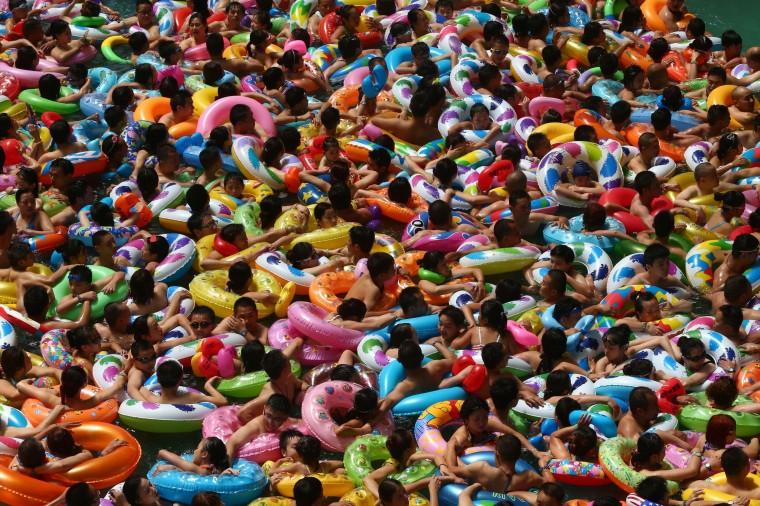 This picture taken on July 25, 2014 shows people cooling off in a waterpark in Suining, southwest China's Sichuan province. Meteorological departments issued an orange alert for high temperature as a heat wave embraces Sichuan province, with temperature of most area topped 37 , local media reported. CHINA OUT/AFP/Getty Images