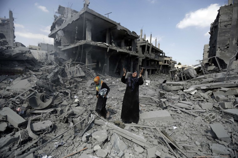 A Palestinian woman pauses amid destroyed buildings in the northern district of Beit Hanun in the Gaza Strip during an humanitarian truce on July 26, 2014. The bodies of at least another 35 Palestinians were recovered from rubble across Gaza during a truce, raising to over 900 the overall death toll of Israel's onslaught on the territory since July 8, medics said. MOHAMMED ABED/AFP/Getty Images