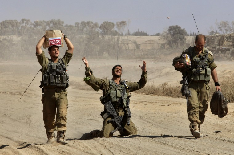 An Israeli soldier gestures in relief as he walks with comrades near the border between Israel and the Gaza Strip after returning from the Hamas-controlled Palestinian coastal enclave, on August 4, 2014. The Israeli army said today it was resuming its strikes on the Gaza Strip, after the end of a seven-hour humanitarian lull. An army spokesman said troops were redeploying within Gaza while other forces were pulling out in a process which began on August 2. GIL COHEN MAGEN/AFP/Getty Images