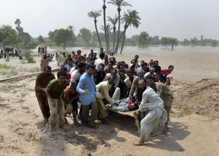 Residents, affected by flooding, wait to board an army helicopter with injured people in the Peer Kot area of Jhang, in central Punjab province on September 11, 2014. Pakistani troops on September 11 rushed to protect two major cities from raging floodwaters, using explosives to divert swollen rivers in a crisis which has hit more than a million people and inundated swathes of farmland. The floods and landslides from days of heavy monsoon rains have now claimed more than 450 lives in Pakistan and India, with hospitals struggling to cope with the disaster. ARIF ALI/AFP/Getty Images