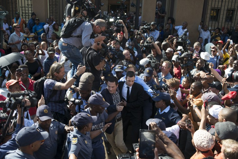 South African Paralympian athlete Oscar Pistorius (C) leaves the High Court after the verdict hearing of his trial over the killing of his model girlfriend Reeva Steenkamp, on September 11, 2014 in Pretoria. Oscar Pistorius was found not guilty of murdering his girlfriend Reeva Steenkamp, a shock decision that left the South African celebrity athlete sobbing with emotion in the dock. The high-profile trial was adjourned until Friday when the 27-year-old Paralympian will hear whether he has been found guilty of culpable homicide, a lesser charge roughly equivalent to manslaughter. MUJAHID SAFODIEN/AFP/Getty Images
